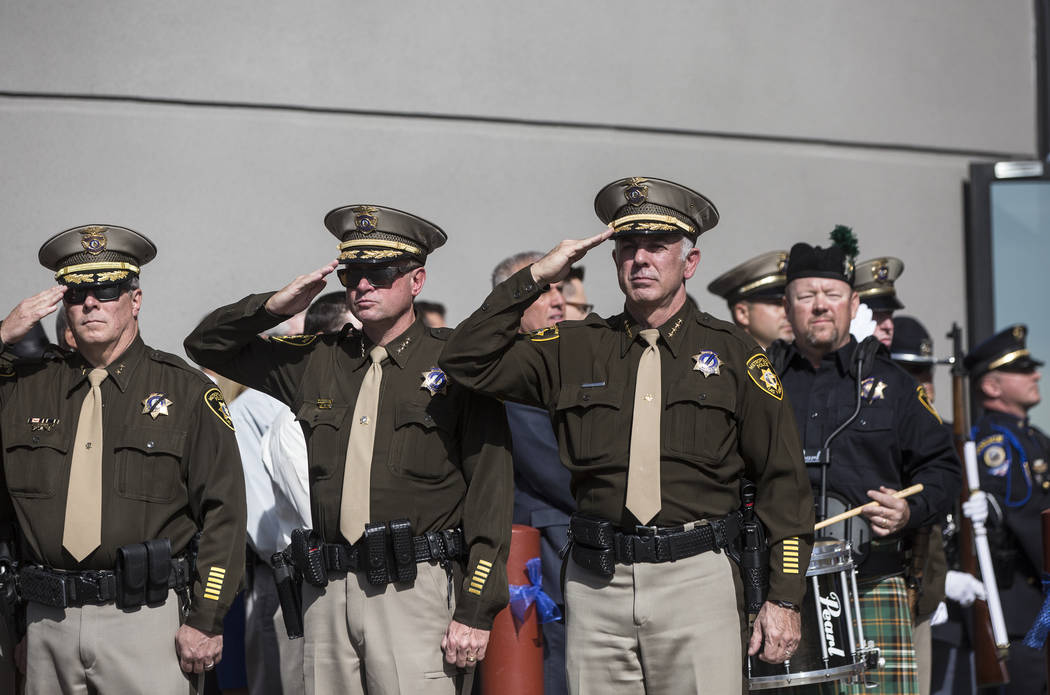 Sheriff Joe Lombardo, right, salutes the funeral procession for Metro officer Charleston Hartfield at Central Church during a service for the off-duty officer killed during the Route 91 shooting o ...