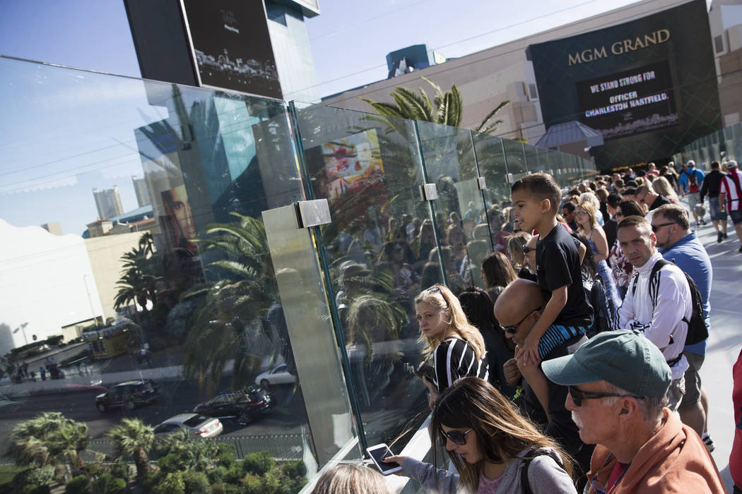People wait for the funeral procession of Las Vegas police officer and Nevada National Guard veteran Charleston Hardfield, at the intersection of Tropicana Ave and Las Vegas Bouelevard in Las Vega ...