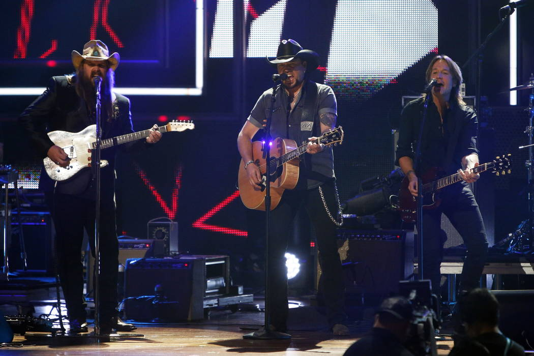 Chris Stapelton, left, Jason Aldean and Keith Urban perform at 2017 CMT Artist of the Year Awards at Nashville's Schermerhorn Symphony Center on Wednesday, Oct. 18, 2017, in Nashville, Tenn. (Phot ...