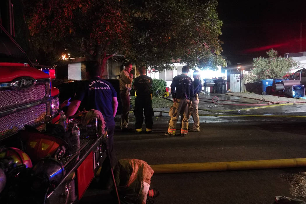 Firefighters gather in front of a home at 365 Wisteria Ave. on Oct. 19 after a house fire that displaced four people. (Max Michor/Las Vegas Review-Journal)
