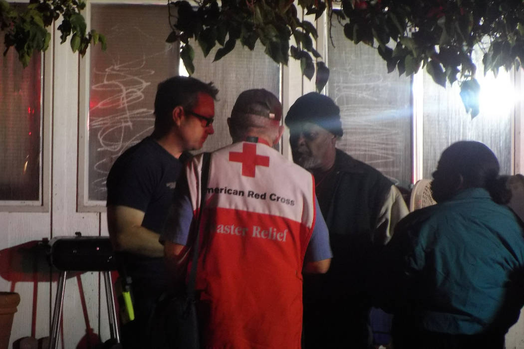 A firefighter and American Red Cross worker speak with residents after an Oct. 19 house fire at 365 Wisteria Ave. (Max Michor/Las Vegas Review-Journal)