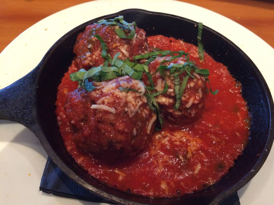 An appetizer of meatballs comes sizzling hot in a miniature cast-iron skillet, choked in marinara sauce. (Jan Hogan/View)