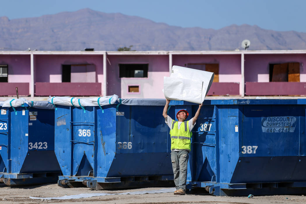 A worker throws a plastic lining over a dumpster as crews clean up remnants of the demolished Moulin Rouge in Las Vegas, Thursday, Oct. 19, 2017. Joel Angel Juarez Las Vegas Review-Journal @jajuar ...