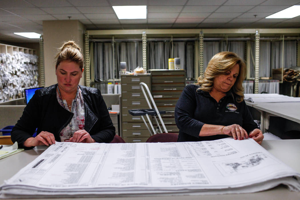 Amy Johnson, 38, an office support specialist, left, and Lorie Suiter, 58, an archives and records technician II, right, lay out public records at the Development Services Records Center at City H ...