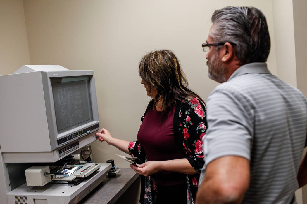 Diane Cottrell, an archives and records technician II, left, shows Steve Loeffler, 51, of Las Vegas, right, a film scan requested through the Development Services Records Center at City Hall in He ...