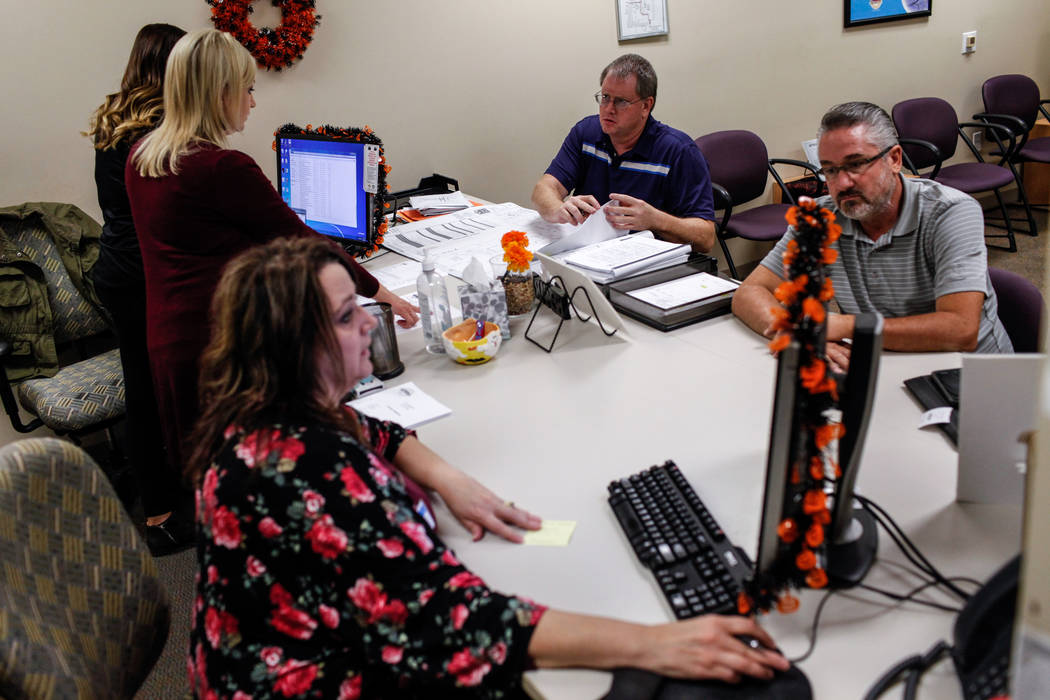 Steve Shaw, 48, of Santa Monica, California, second from right, and Steve Loeffler, 51, of Las Vegas, right, are helped by employees at the Development Services Records Center for public records r ...