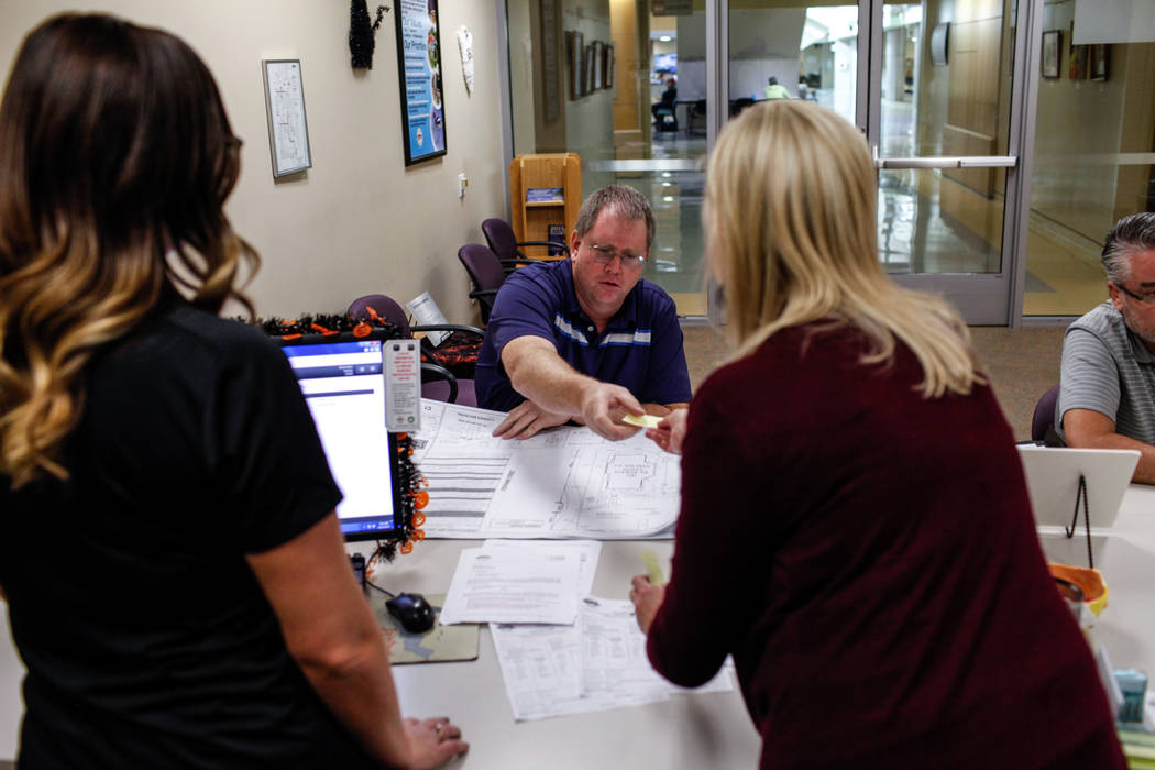 Steve Shaw, 48, of Santa Monica, California, center, is helped by employees at the Development Services Records Center for public records requests at City Hall in Henderson, Tuesday, Oct. 24, 2017 ...