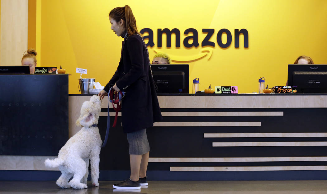 In this Wednesday, Oct. 11, 2017, photo, an Amazon employee gives her dog a biscuit as the pair head into a company building, where dogs are welcome, in Seattle. (AP Photo/Elaine Thompson)