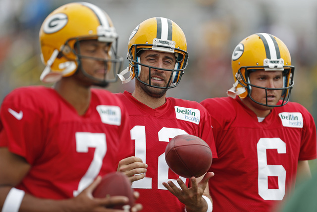 Green Bay Packers quarterback Aaron Rodgers (12) spins the ball on his finger while he and quarterbacks Brett Hundley (7) Joe Callahan (6) participate in drills during NFL football training camp,  ...