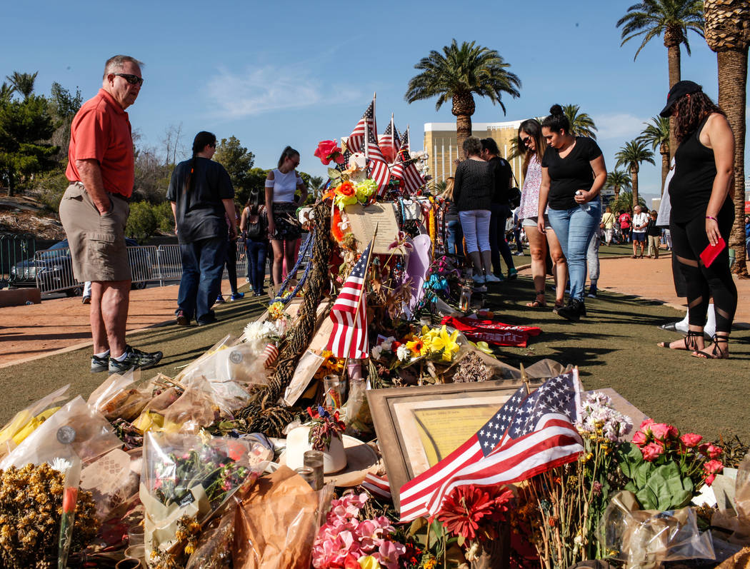 Steve Adams of Colorado and Henderson, 68, left, visits a memorial at the Welcome to Fabulous Las Vegas sign in Las Vegas, Monday, Oct. 16, 2017, honoring the victims of the Route 91 Harvest Festi ...