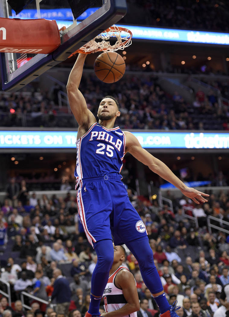 Philadelphia 76ers guard Ben Simmons dunks over Washington Wizards guard Tim Frazier, rear, during the first half of an NBA basketball game, Wednesday, Oct. 18, 2017, in Washington. (AP Photo/Nick ...