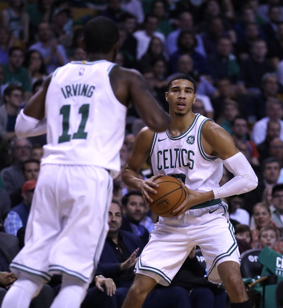 Boston Celtics forward Jayson Tatum, right, sets to pass to Kyrie Irving (11) during the first quarter of an NBA basketball game, Wednesday, Oct. 18, 2017, in Boston. (AP Photo/Charles Krupa)