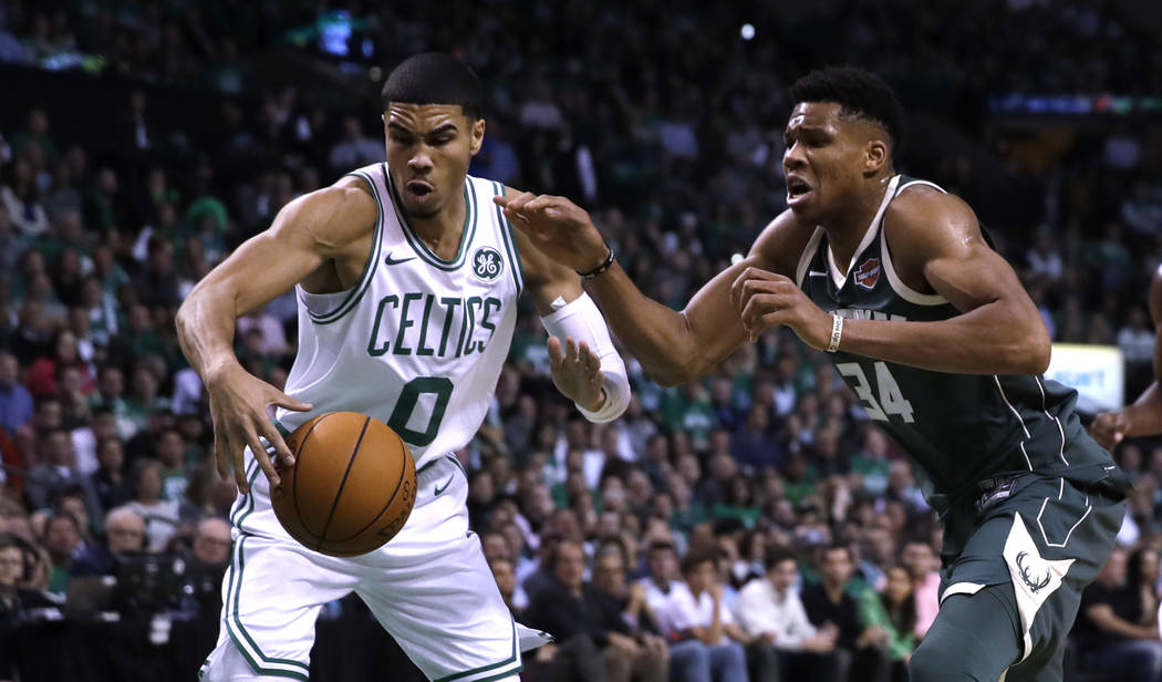 Boston Celtics forward Jayson Tatum (0) battles Milwaukee Bucks forward Giannis Antetokounmpo (34) for the ball during the first quarter of an NBA basketball game, Wednesday, Oct. 18, 2017, in Bos ...