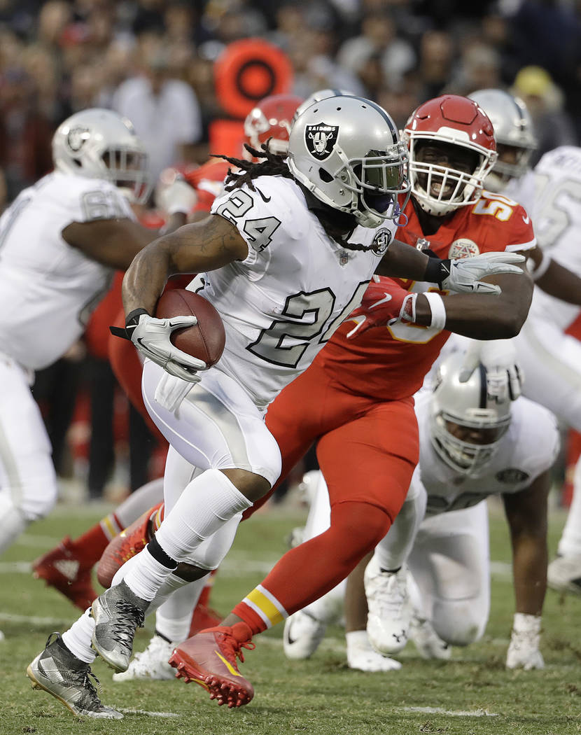 Oakland Raiders running back Marshawn Lynch (24) runs against Kansas City Chiefs outside linebacker Justin Houston (50) during the first half of an NFL football game in Oakland, Calif., Thursday,  ...