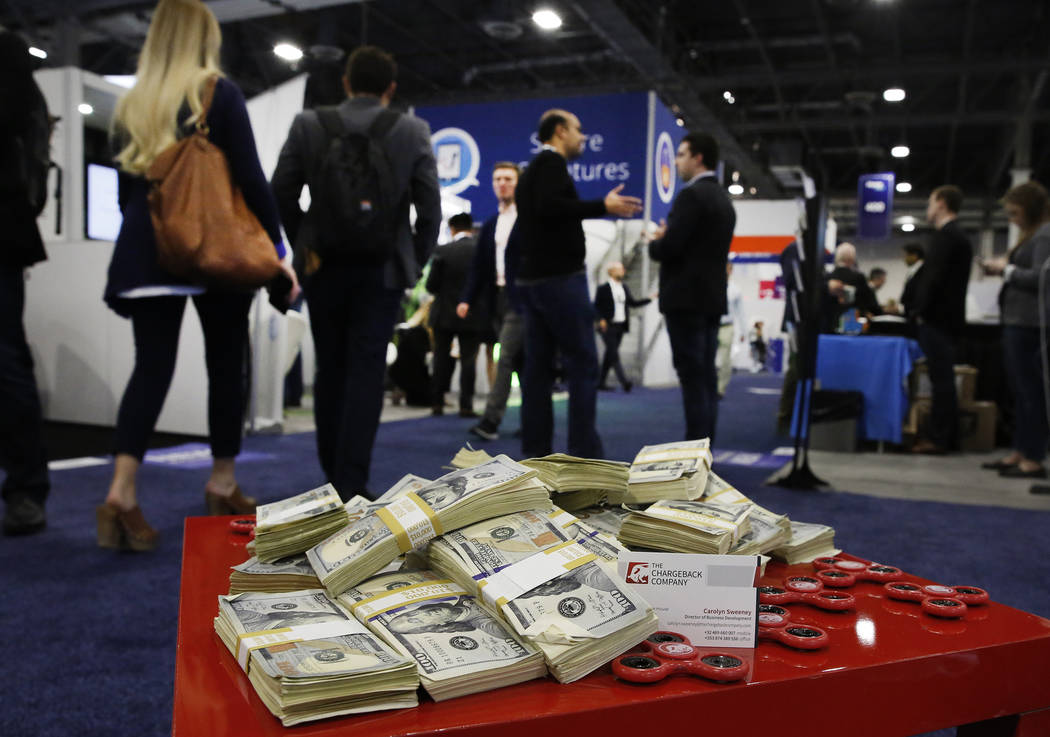 Attendees walk past fake paper play money during the 2017 Money 20/20 conference at the Sands Expo and Convention Center Monday, Oct. 23, 2017, in Las Vegas. Bizuayehu Tesfaye Las Vegas Review-Jou ...