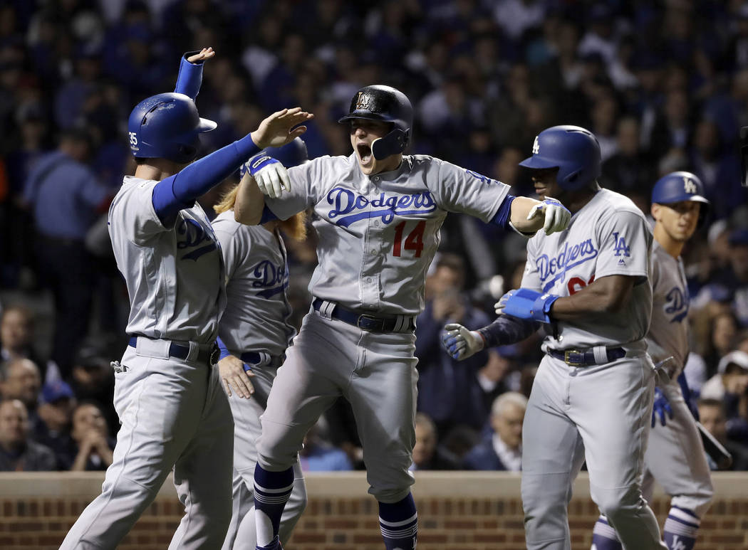 Los Angeles Dodgers' Enrique Hernandez (14) celebrates after hitting a grand slam during the third inning of Game 5 of baseball's National League Championship Series against the Chicago Cubs, Thur ...
