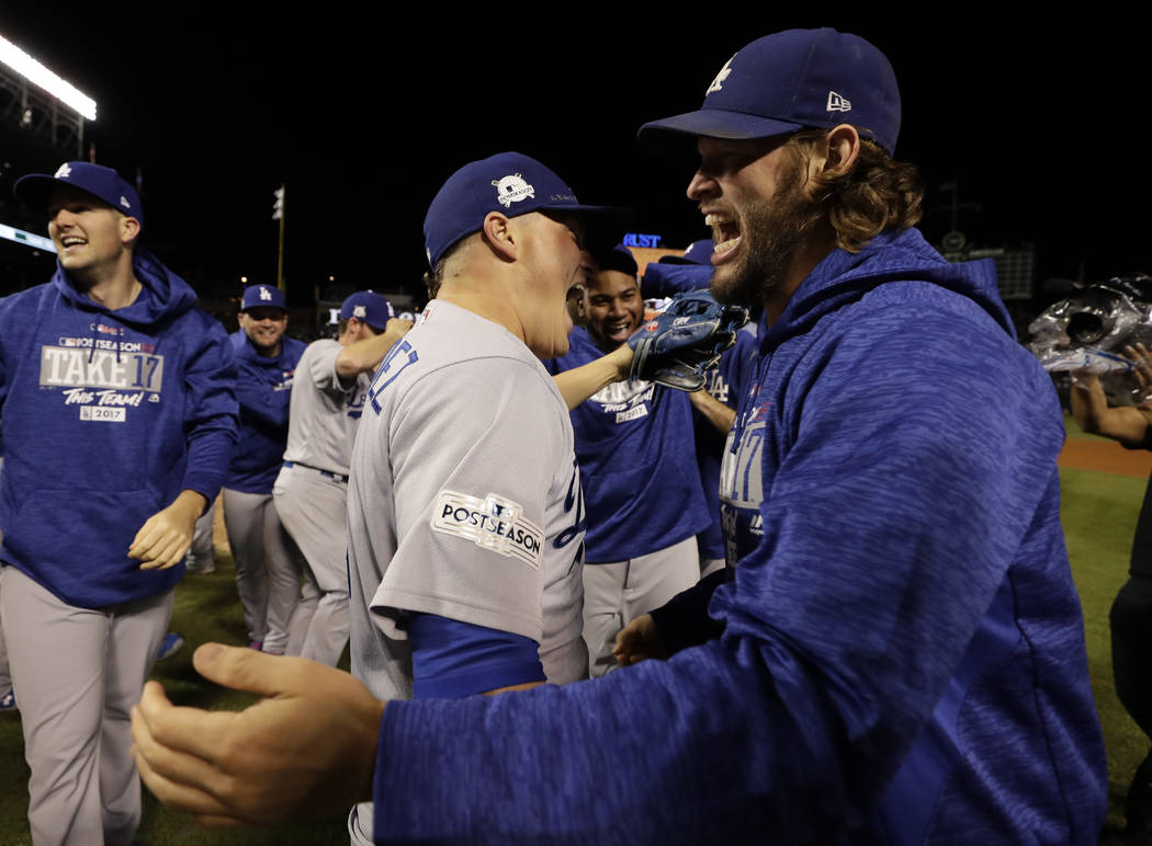 Los Angeles Dodgers' Enrique Hernandez and Clayton Kershaw celebrate after Game 5 of baseball's National League Championship Series against the Chicago Cubs, Thursday, Oct. 19, 2017, in Chicago. T ...