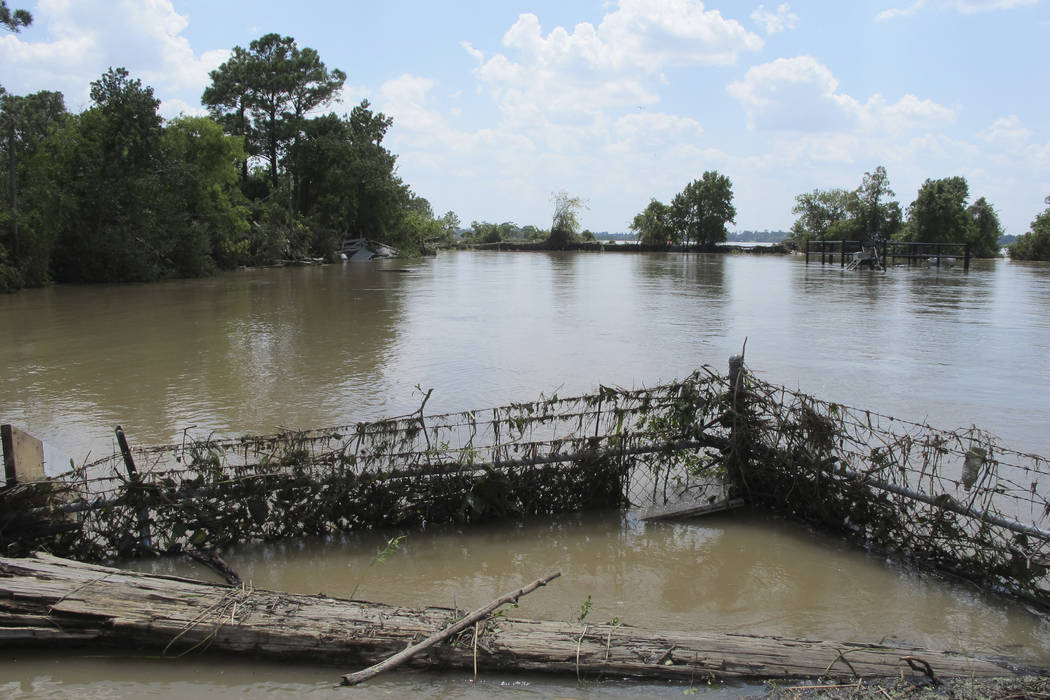 FILE - In this Aug. 31, 2017 file photo, a barbed-wire fence encircles the Highlands Acid Pit that was flooded by water from the nearby San Jacinto River as a result from Harvey in Highlands, Texa ...