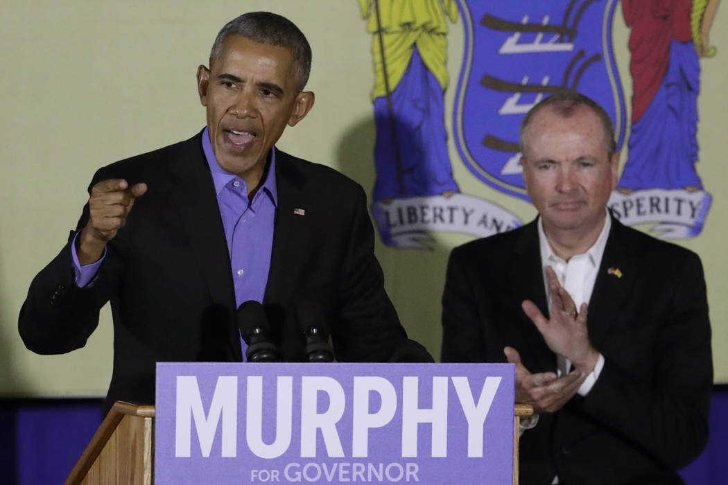 Former President Barack Obama, left, speaks during a canvassing event for New Jersey Democratic gubernatorial nominee Phil Murphy, right, Thursday, Oct. 19, 2017, in Newark, N.J. (AP Photo/Julio C ...