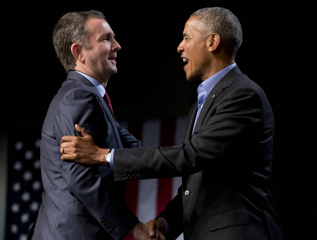 Former President Barack Obama, right, greets Virginia's Democratic gubernatorial candidate Lt. Gov. Ralph Northam during a rally in Richmond, Va., Thursday, Oct. 19, 2017. (AP Photo/Steve Helber)