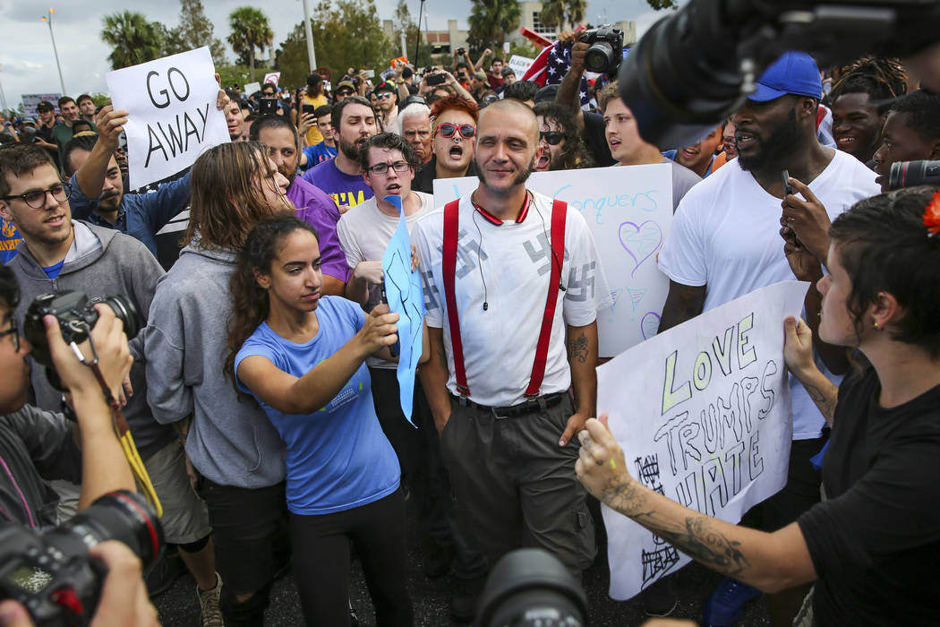 Protesters confront a man wearing a shirt with swastikas outside a University of Florida auditorium where white nationalist Richard Spencer was preparing to speak, Thursday, Oct. 19, 2017 in Gaine ...
