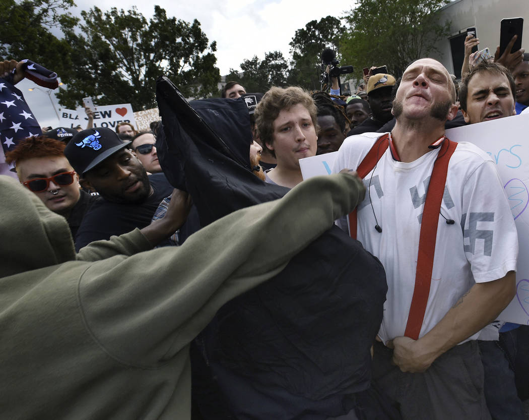 Randy Furniss, of Idaho, recoils after getting punched in the face as he walks through a crowd of protesters outside a University of Florida auditorium where white nationalist Richard Spencer was  ...