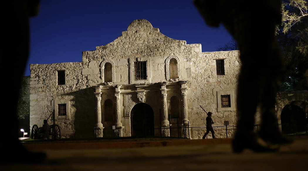 In this March 6, 2013 file photo, Dan Phillips, a member of the San Antonio Living History Association, patrols the Alamo during a pre-dawn memorial ceremony to remember the 1836 Battle of the Ala ...
