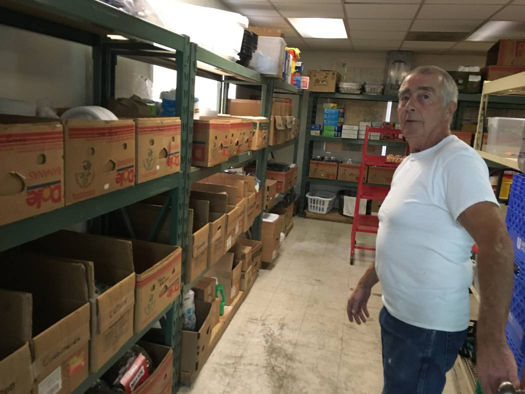 Peter Montgomery, a regular volunteer at St. Timothy's, stands next to boxes holding different hygiene products and clothes people can ask for after dinner. In the boxes are items like mouth wash, ...