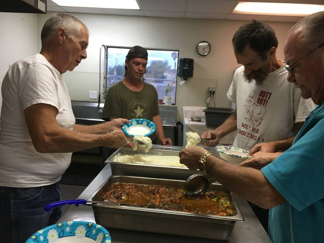 Volunteers Peter Montgomery (left) and Allan Howe (right), alongside two men, John Ficcone and Jerome Isaac who have frequented the church's program for years and now often help serve and clean du ...