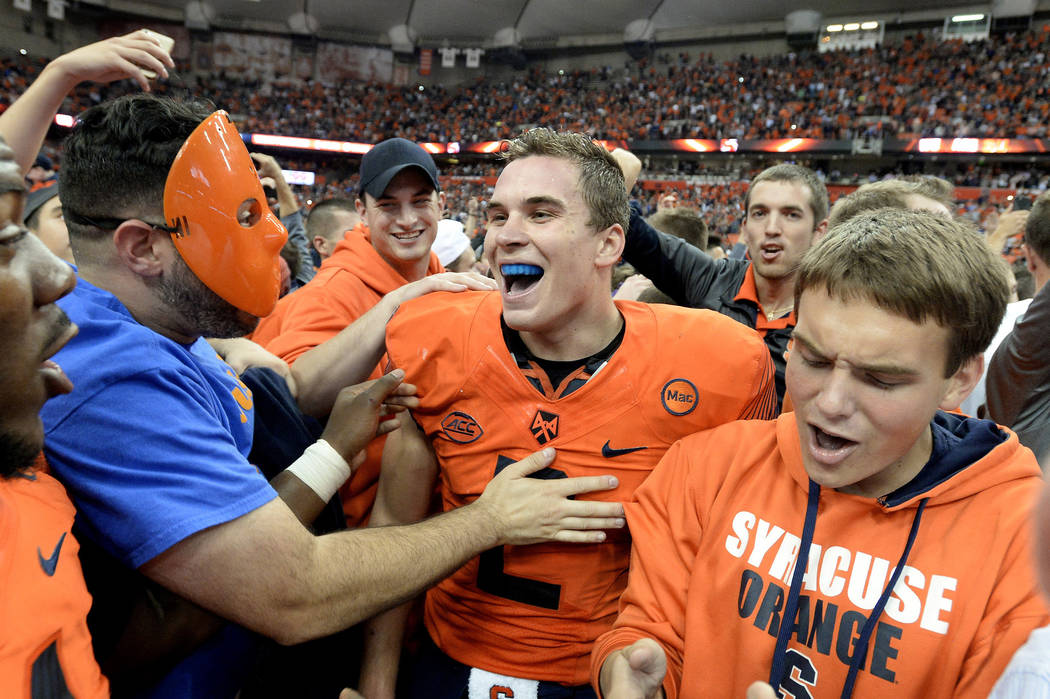 FILE - In this Friday, Oct. 13, 2017, file photo, Syracuse quarterback Eric Dungey center, celebrates with fans after Syracuse's 27-24 win over Clemson in an NCAA college football game in Syracuse ...