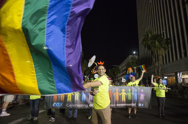 The leader of the Cox Communications entry waives a pride flag at the 18th Annual Las Vegas PRIDE Night Parade in downtown Las Vegas on Friday, Oct. 21, 2016. Richard Brian/Las Vegas Review-Journa ...