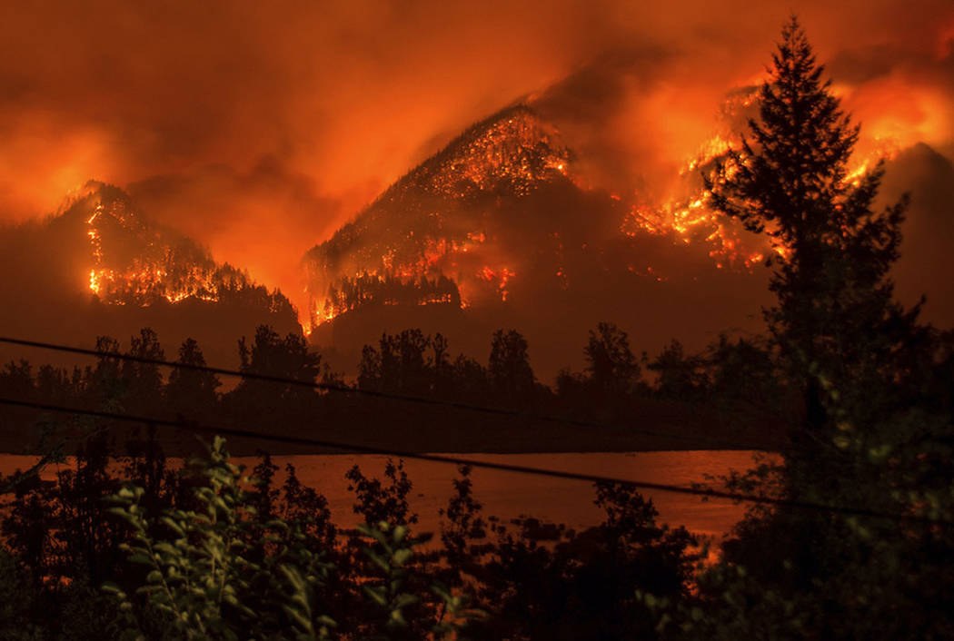 A wildfire is seen from Stevenson, Wash., across the Columbia River, burning in the Columbia River Gorge above Cascade Locks, Ore., in September. (Tristan Fortsch/KATU-TV via AP, File)