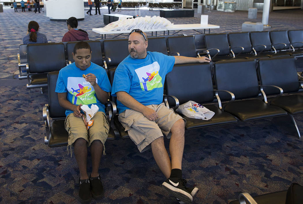 Shamar Anter, 16, left, with his father Chris, after boarding  an Allegiant plane during the Wings for Autism event at McCarran International Airport in Las Vegas, Saturday, Oct. 21, 2017. Erik Ve ...