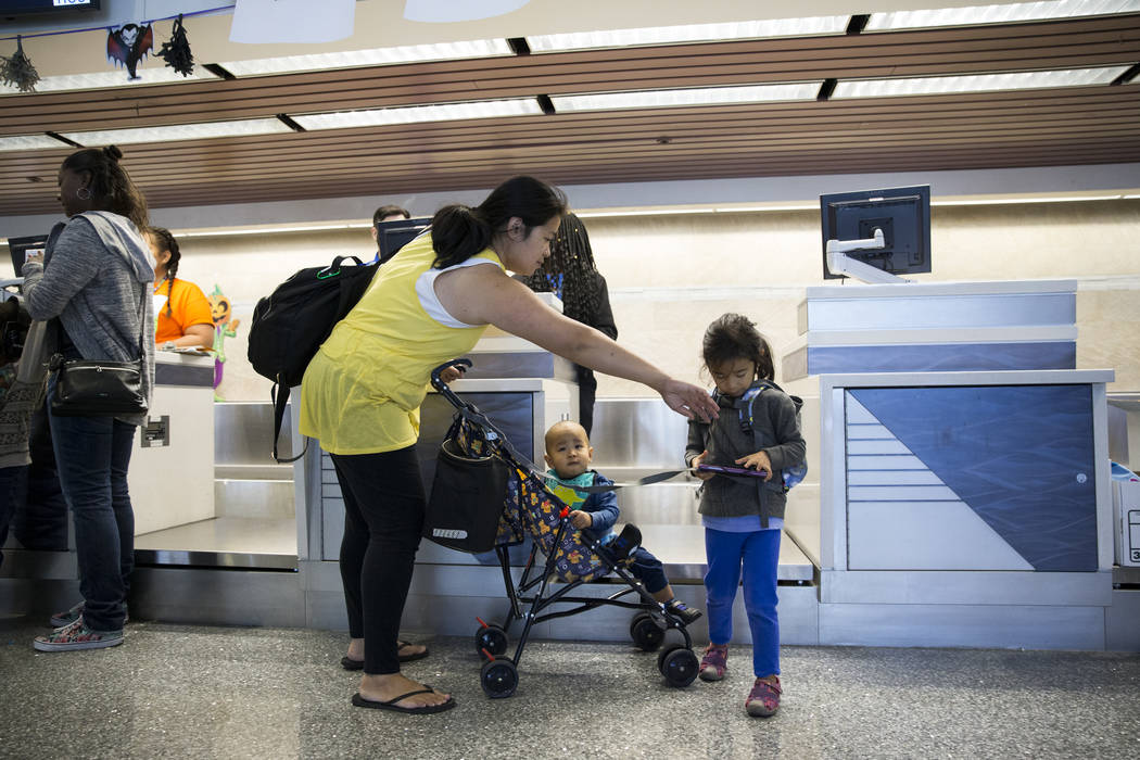 Linda Hua with her children Leiland, 1, and Leilani, 5, in the Allegiant ticketing desk during the Wings for Autism event at McCarran International Airport in Las Vegas, Saturday, Oct. 21, 2017. E ...