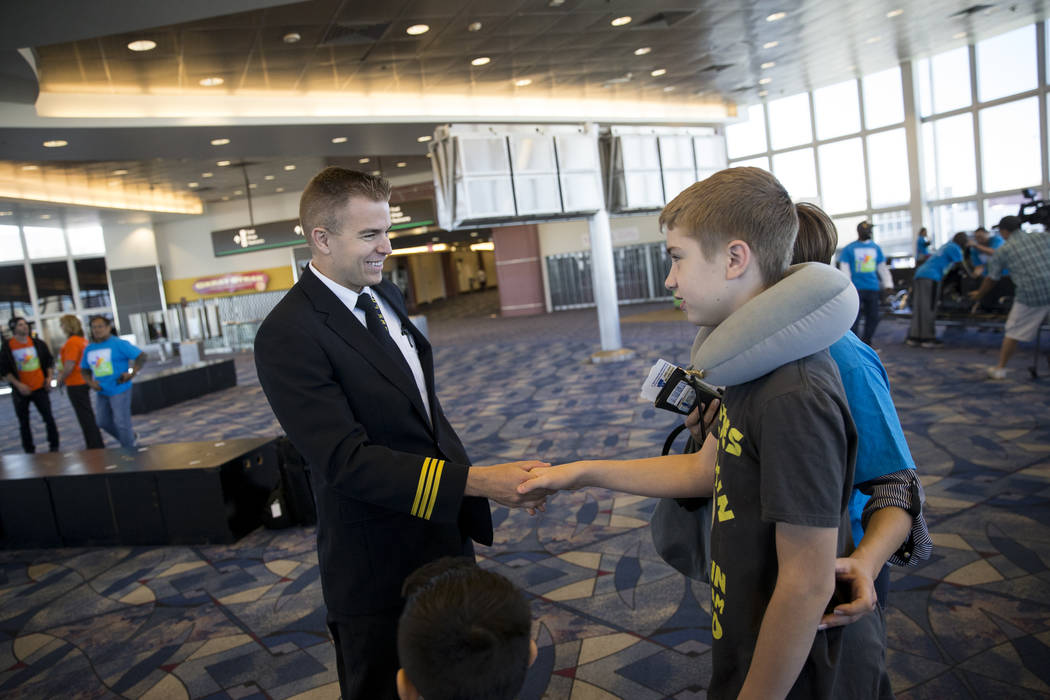 Allegiant First Officer Frederick Landgraf shakes hands with  Lucas Reisman, 13, of Las Vegas, before boarding a plane during the Wings for Autism event at McCarran International Airport in Las Ve ...