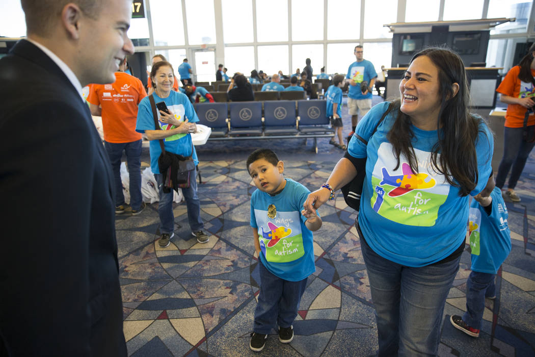 Allegiant First Officer Frederick Landgraf, far left, speaks with Angela Valerio, and her two children, Bejanmin Cobian-Valerio, 5, second from left, and Theodore, 4, during the Wings for Autism e ...