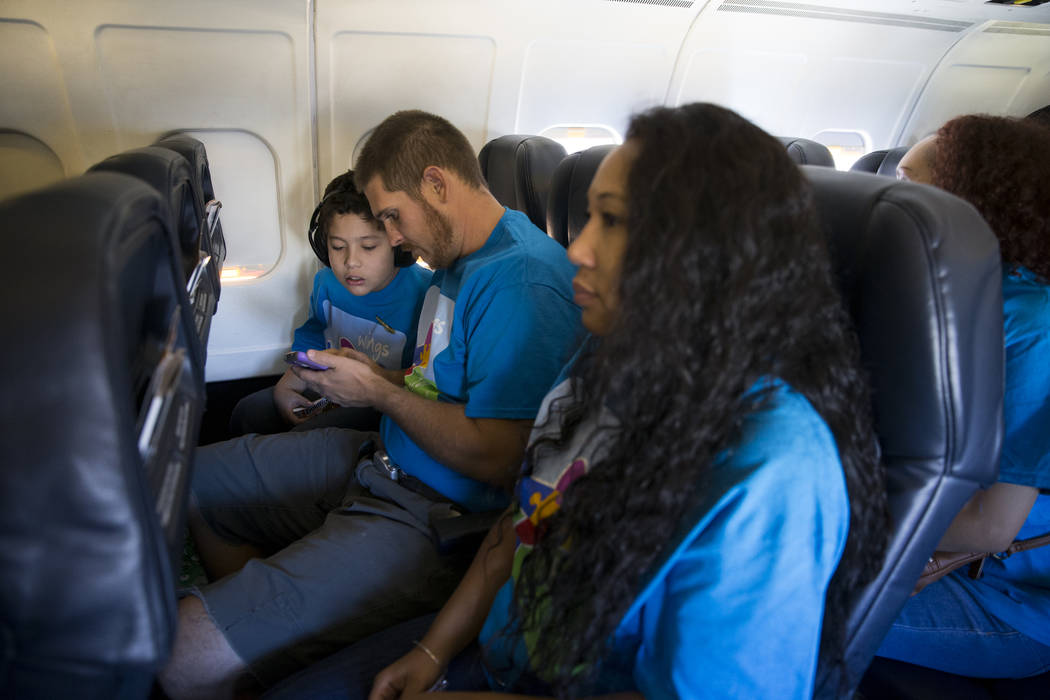 Isaiah Peach, 11, from left, with his parents Nick Panegasser, and mother Carrie Peach, of Las Vegas, on board of an Allegiant plane during the Wings for Autism event at McCarran International Air ...