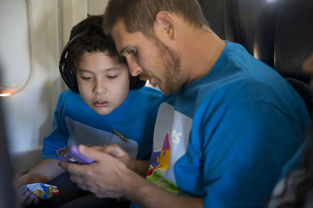 Isaiah Peach, 11, with his father Nick Panegasser, on board of an Allegiant plane during the Wings for Autism event at McCarran International Airport in Las Vegas, Saturday, Oct. 21, 2017. Erik Ve ...