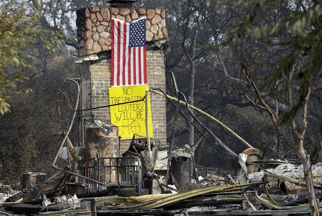 A sign on the chimney of a home warns looters Wednesday, Oct. 18, 2017, after it was destroyed by wildfires in Glen Ellen, Calif. California fire officials have reported significant progress on co ...