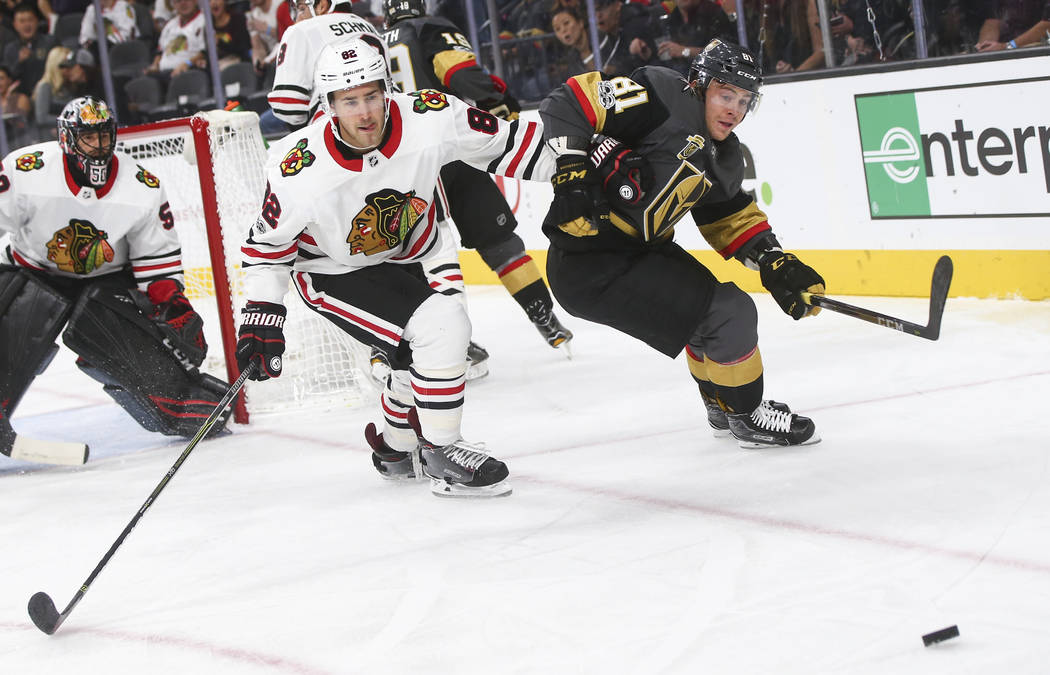 Chicago Blackhawks' Jordan Oesterle (82) and Golden Knights' Jonathan Marchessault (81) go after the puck during an NHL hockey game at T-Mobile Arena in Las Vegas on Tuesday, Oct. 24, 2017. Chase  ...