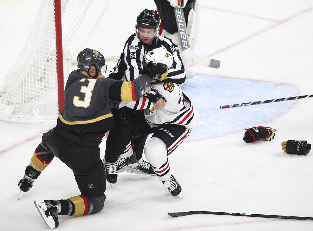 An official stops a fight between Golden Knights' Brayden McNabb (3) and Chicago Blackhawks' Ryan Hartman (38) during an NHL hockey game at T-Mobile Arena in Las Vegas on Tuesday, Oct. 24, 2017. C ...