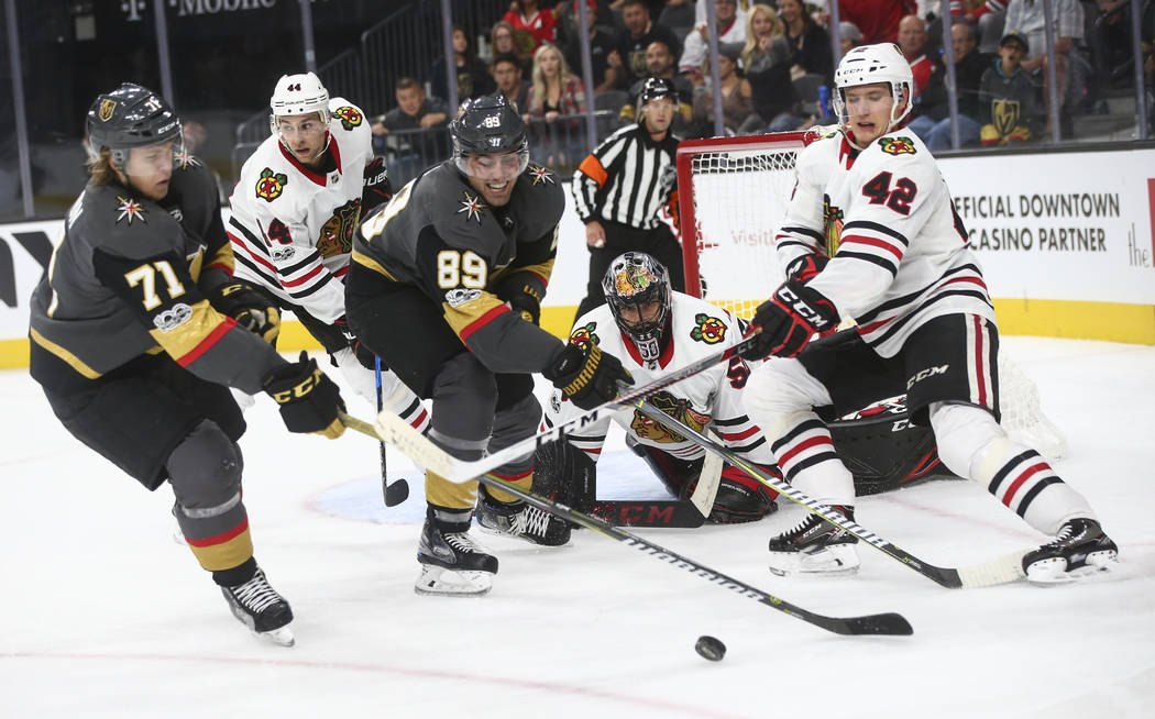 Golden Knights' Alex Tuch (89) and William Karlsson (71) battle for the puck against Chicago Blackhawks' Gustav Forsling (42) during an NHL hockey game at T-Mobile Arena in Las Vegas on Tuesday, O ...