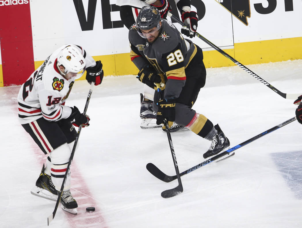 Chicago Blackhawks' Alex DeBrincat (12) and Golden Knights' William Carrier (28) battle for the puck during an NHL hockey game at T-Mobile Arena in Las Vegas on Tuesday, Oct. 24, 2017. Chase Steve ...
