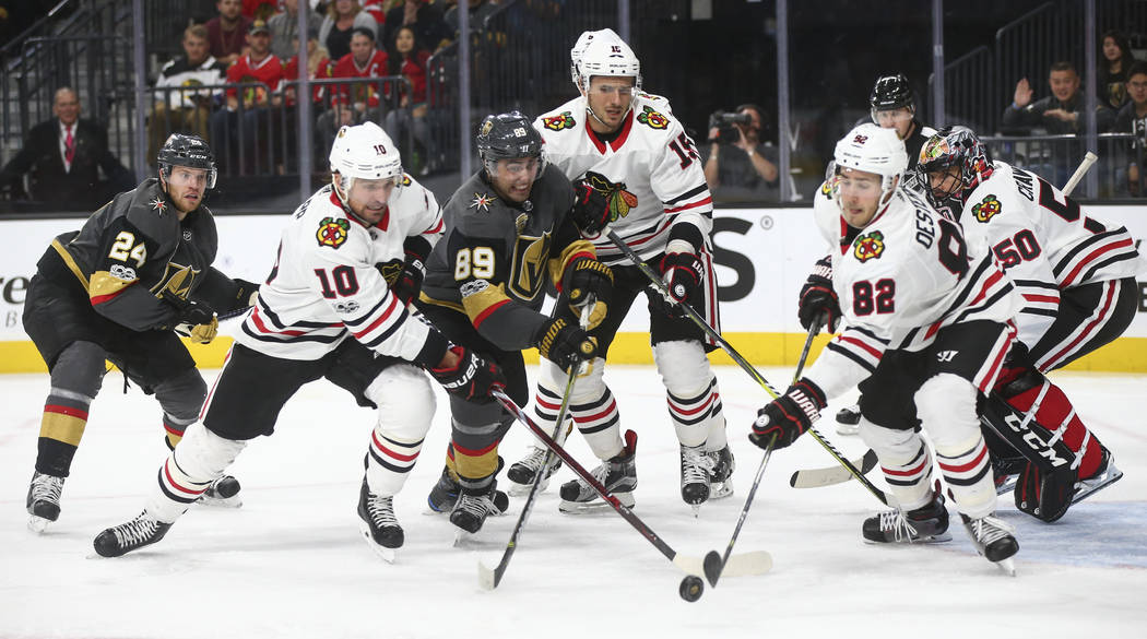 Golden Knights' Alex Tuch (89) battles for the puck against Chicago Blackhawks' Patrick Sharp (10) and Jordan Oesterle (82) during an NHL hockey game at T-Mobile Arena in Las Vegas on Tuesday, Oct ...