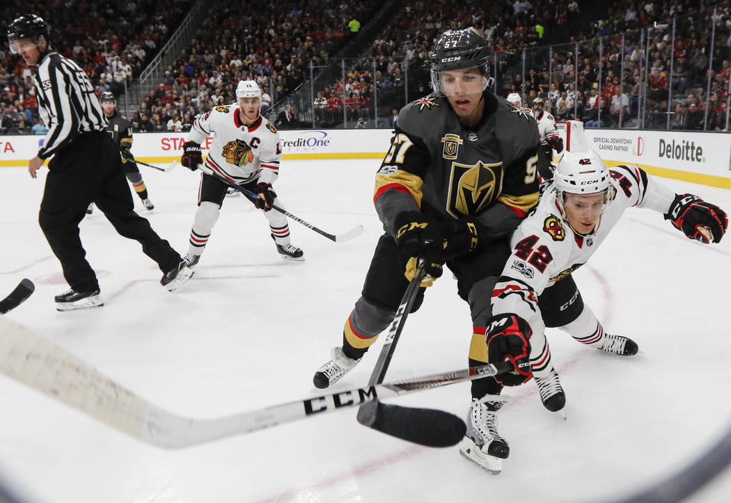 Golden Knights' David Perron (57) and Chicago Blackhawks' Gustav Forsling (42) go after the puck during an NHL hockey game at T-Mobile Arena in Las Vegas on Tuesday, Oct. 24, 2017. Chase Stevens L ...