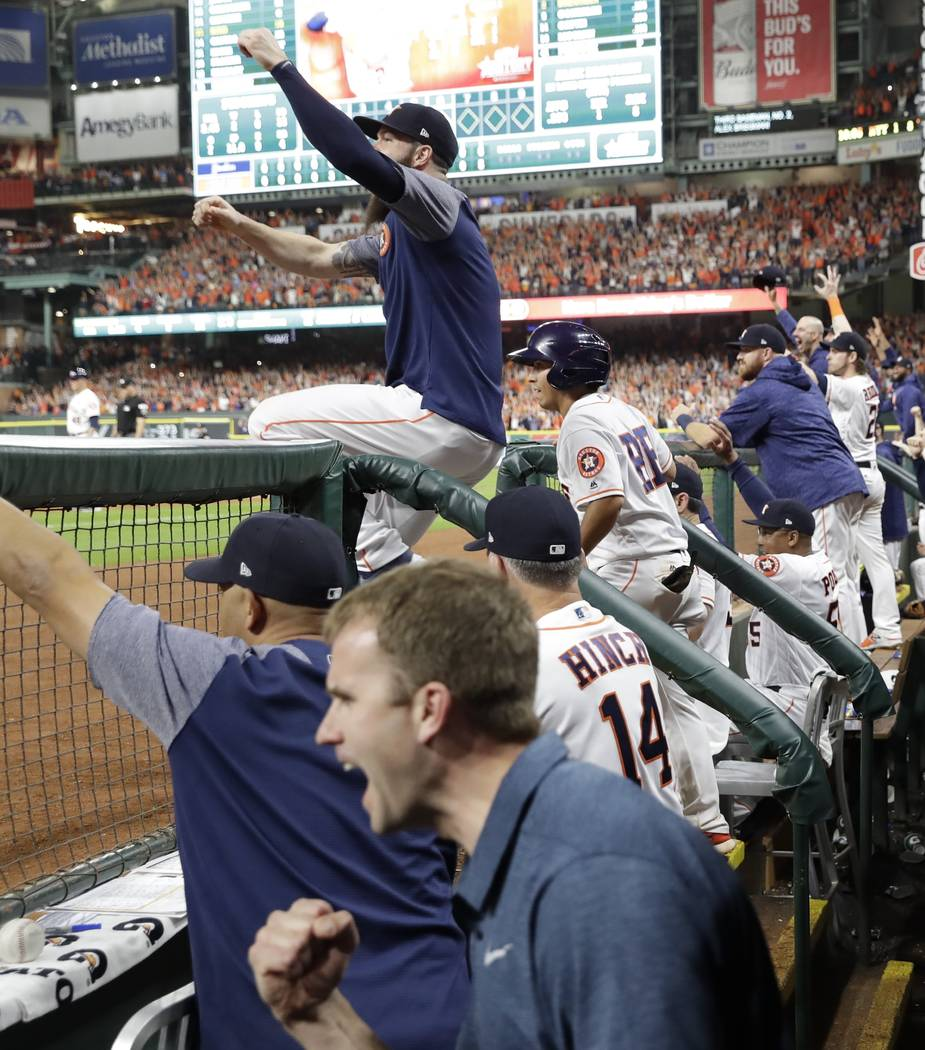 The Houston Astros dugout reacts after a home run hit by Jose Altuve during the eighth inning of Game 6 of baseball's American League Championship Series against the New York Yankees Friday, Oct.  ...