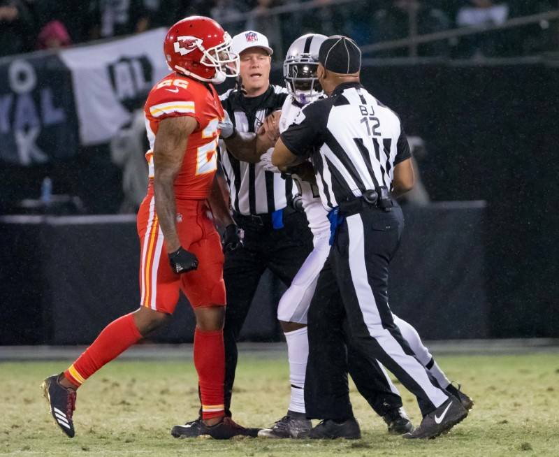 Referees break up an altercation between the Kansas City Chiefs cornerback Marcus Peters (22) and Oakland Raiders running back Marshawn Lynch (24) during the second quarter at Oakland Coliseum, Oc ...