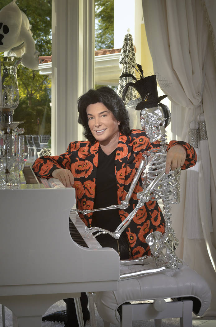 """Las Vegas entertainer Frank Marino poses with the new addition to his Halloween collection, """"Mr. Bone-Jangles,"""" who is seated at the Steinway piano. (Bill Hughes Real Estate Millions)"""