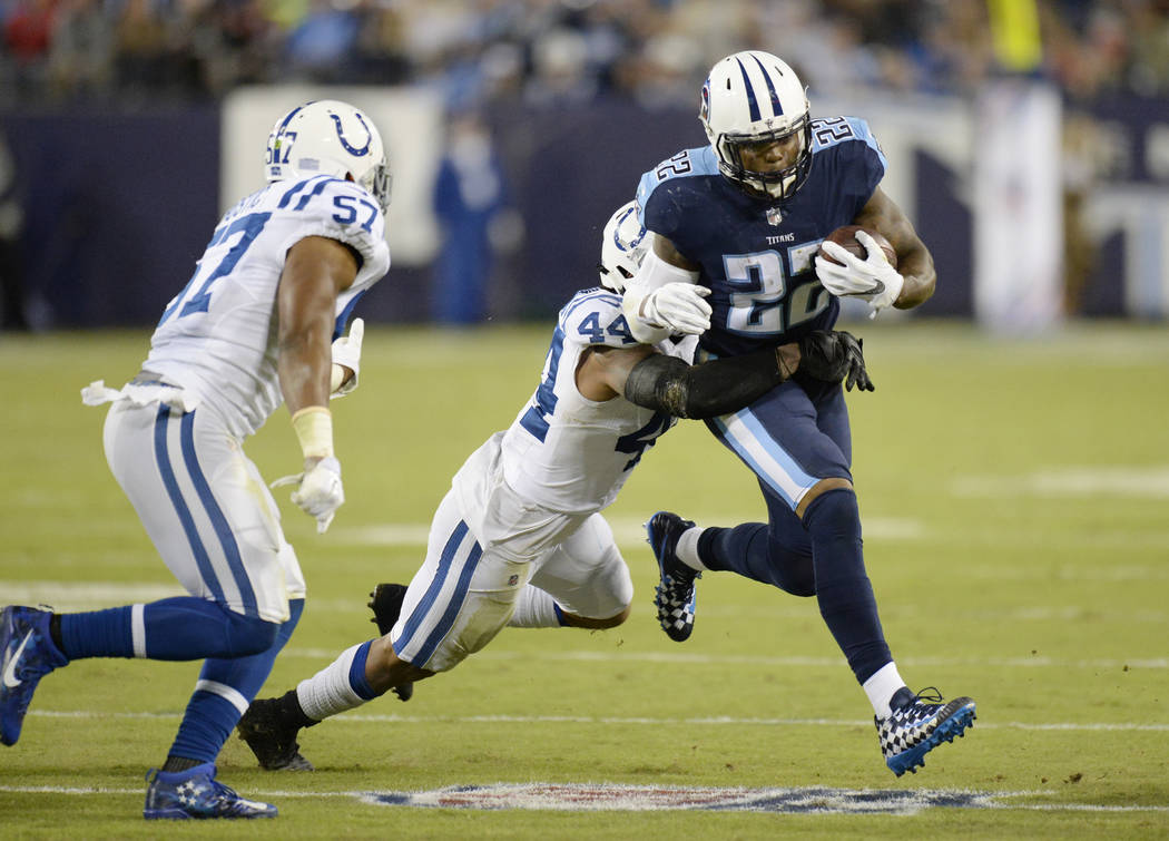 Tennessee Titans running back Derrick Henry (22) runs the ball against Indianapolis Colts inside linebacker Antonio Morrison (44) and inside linebacker Jon Bostic (57) in the first half of an NFL  ...