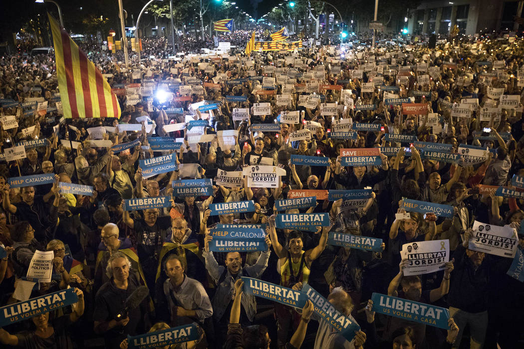 Holding signs reading in Catalan 'freedom', people gather to protest against the National Court's decision to imprison civil society leaders without bail, in Barcelona, Spain, Tuesday, Oct. 17, 20 ...